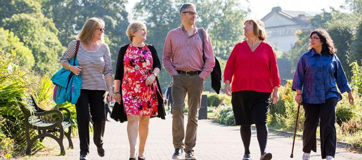 Four women and a man walking along a footpath in a park on a sunny day.