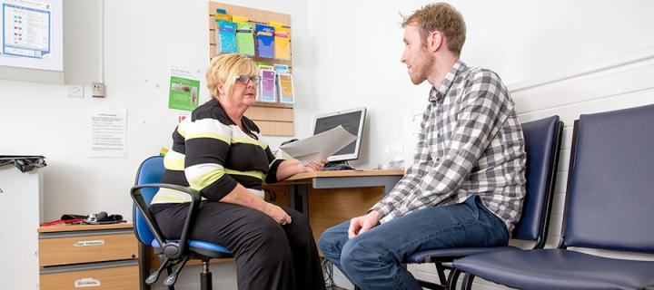 A mature woman, a member of staff and a young male patient sitting in a consultation room.